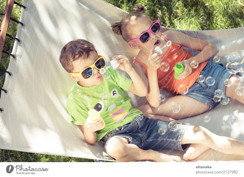 Zwei glückliche Kinder liegen auf einer Hängematte und spielen mit Seifenblasen. Mensch Natur Sommer schön grün Sonne Erholung Freude Lifestyle lustig Liebe