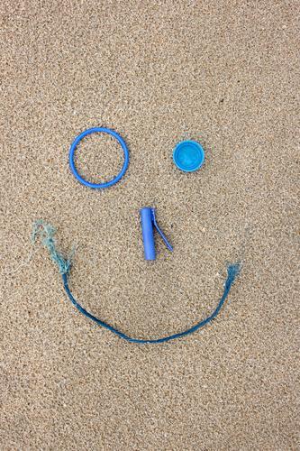 Plastik Strand-Fundstücke als lachendes Gesicht blau Freude Umwelt Spielen Sand Fröhlichkeit Zukunft kaputt Coolness Kunststoff Sammlung Müll machen