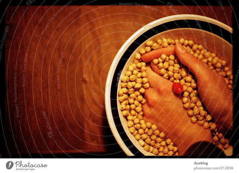 Kichererbsen Hand rot gelb Ernährung Gefühle Lebensmittel Holz braun Haut Finger Tisch Punkt Schalen & Schüsseln Bildausschnitt Textfreiraum links Erbsen