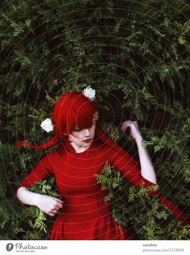 Junge Frau mit dem roten Haar und roten dem Kleid, das auf Blättern liegt Mensch Jugendliche Farbe schön grün Blume Einsamkeit Blatt 18-30 Jahre Erwachsene