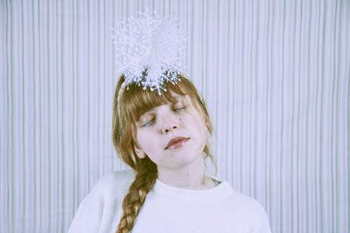 Junge blonde Frau mit einer Schneeflocke über ihrem Kopf Lifestyle Stil Erholung ruhig Winter Winterurlaub Feste & Feiern Weihnachten & Advent