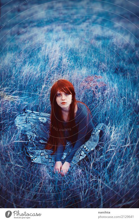 Junge Rothaarigefrau, die auf einem Feld des blauen Grases sitzt Mensch Natur Jugendliche Junge Frau schön rot Einsamkeit ruhig 18-30 Jahre Erwachsene Wiese