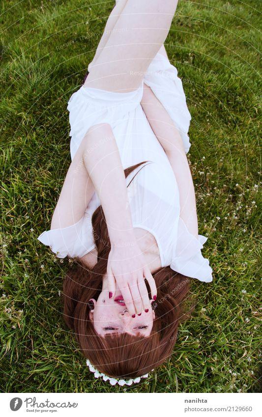 Junge Frau, die sich auf einem Gebiet des Grases hinlegt Lifestyle elegant Stil schön Mensch feminin Jugendliche 1 18-30 Jahre Erwachsene Natur Pflanze Frühling