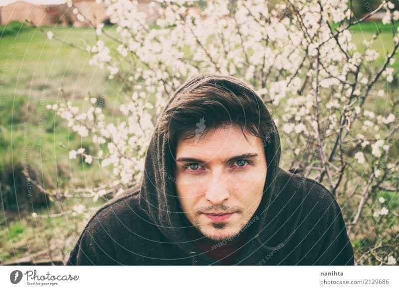 Junger Mann, der mit weißen Blumen als Hintergrund aufwirft Lifestyle Mensch maskulin Jugendliche 1 18-30 Jahre Erwachsene Natur Pflanze Frühling Klima
