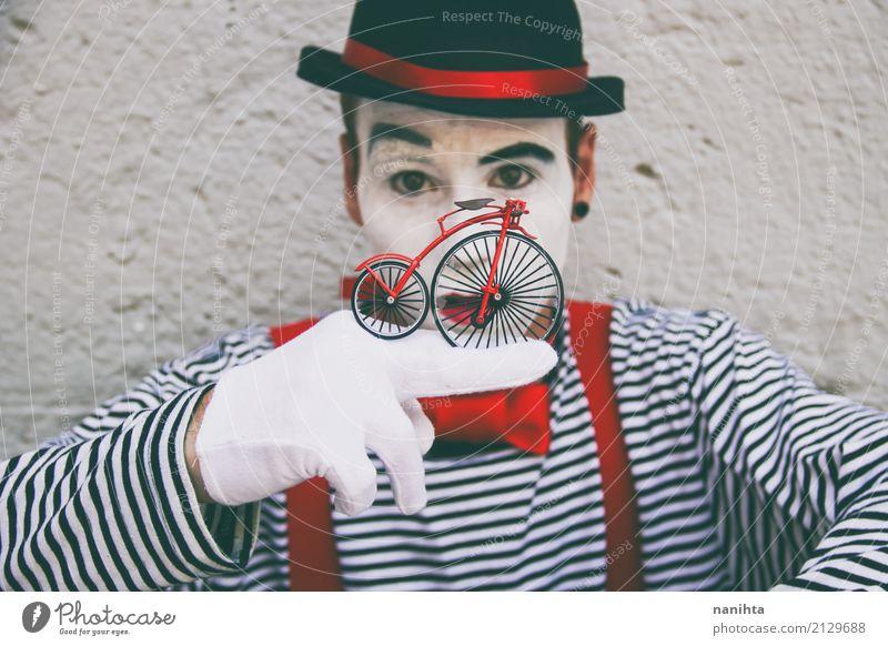 Junger Mann mit einem Clownkostüm hält ein kleines Fahrrad Stil Feste & Feiern Karneval Halloween Mensch maskulin Jugendliche 1 18-30 Jahre Erwachsene Zirkus