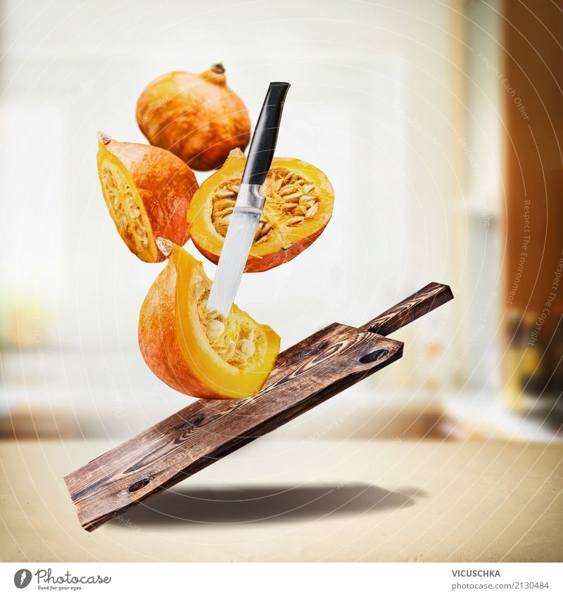 Fliegendes Kürbis mit Schneidebrett und Messer am Küchentisch Gesunde Ernährung Foodfotografie Essen Leben Herbst Stil Lebensmittel Design Häusliches Leben