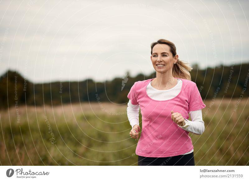 Nette Frau, die durch Feld läuft Mensch Natur Sommer Gesicht Erwachsene Lifestyle Herbst Sport Textfreiraum blond Aktion Lächeln Fitness reif Läufer
