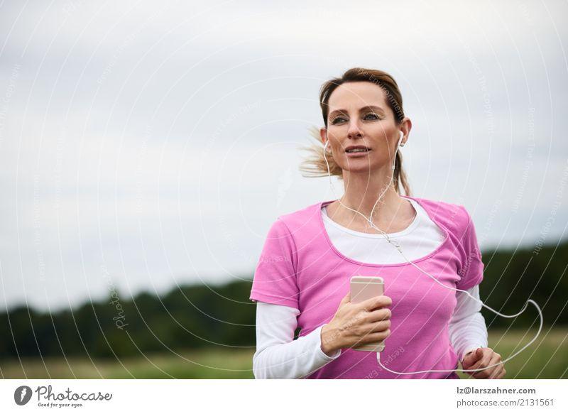 Starke Frau, die durch Feld läuft Lifestyle Gesicht Sommer Musik Sport Joggen PDA Erwachsene 1 Mensch 30-45 Jahre Natur Herbst blond Fitness hören rennen
