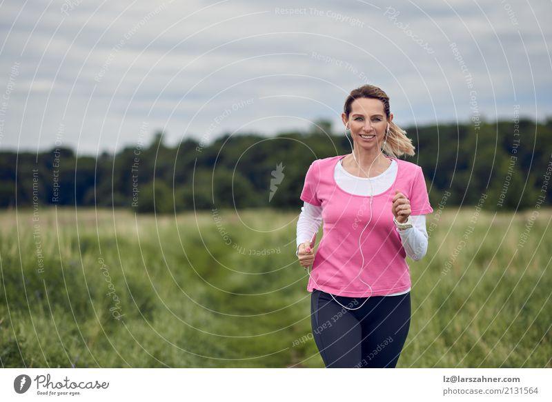 Nette Frau, die durch Feld läuft Lifestyle Gesicht Sommer Musik Sport Joggen PDA Erwachsene 1 Mensch 30-45 Jahre Natur Herbst blond Fitness hören Lächeln