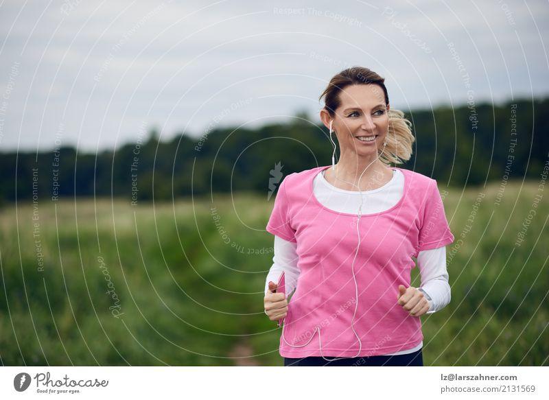 Nette Frau, die durch Feld läuft Mensch Natur Sommer Gesicht Erwachsene Lifestyle Herbst Sport Textfreiraum blond Musik Aktion Lächeln Fitness hören