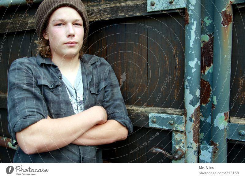 türsteher maskulin Junger Mann Jugendliche Arme Hemd Mütze Coolness Kraft Sicherheit Eingang Eingangstor Schüler verweigern stark Holztor Blick Kontrolle