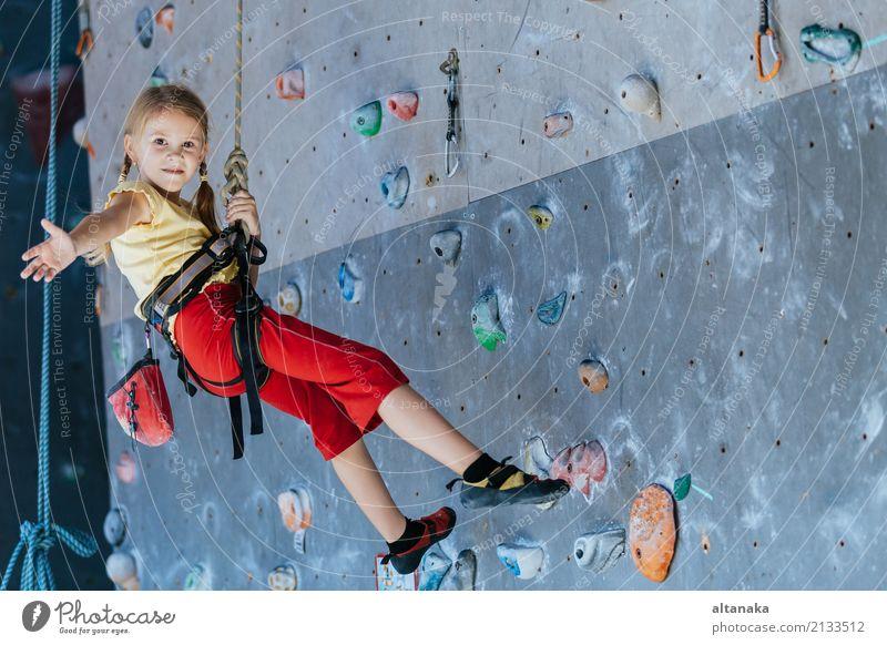 kleines Mädchen, das eine Innenwand der Felsen klettert. Freude Freizeit & Hobby Spielen Ferien & Urlaub & Reisen Abenteuer Camping Entertainment Sport Klettern