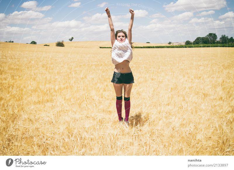 Junge Frau, die auf einem Gebiet des Weizens springt Lifestyle Freude Wellness Leben Ferien & Urlaub & Reisen Sommer Sommerurlaub Sonne Erfolg Mensch feminin