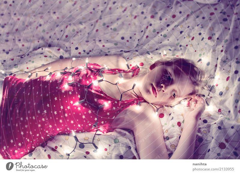 Junge Frau, die in ihrem Bett bedeckt mit Weihnachtslichtern liegt Lifestyle Lampe Schlafzimmer Weihnachten & Advent Silvester u. Neujahr Mensch feminin