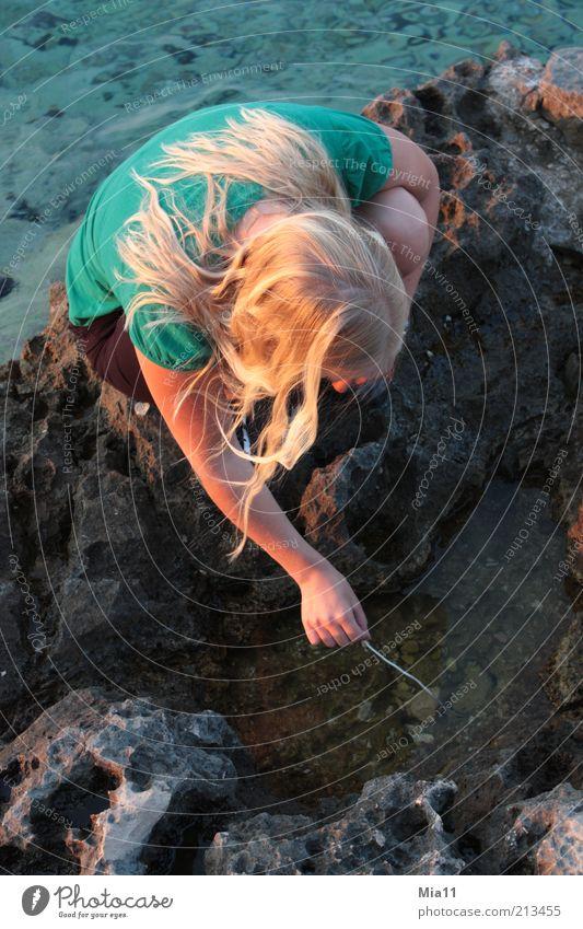 Was versteckt sich da? Frau Mensch Natur Jugendliche Wasser Meer Sommer feminin Spielen Stein braun Küste blond Erwachsene Suche