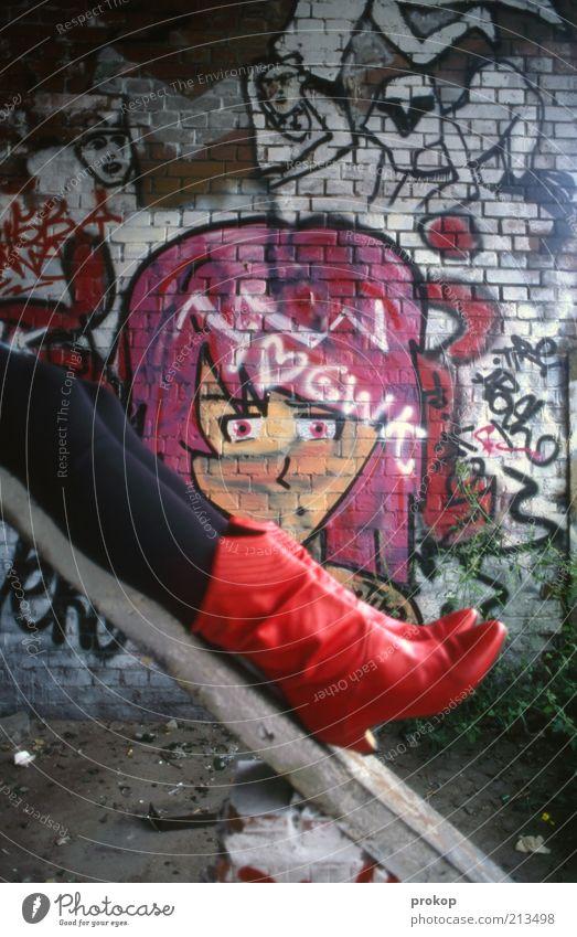 Rote Stiefel mit Gesicht Lifestyle Mensch feminin Junge Frau Jugendliche Erwachsene Mauer Wand Mode liegen Coolness Glück rebellisch schön Lebensfreude bizarr