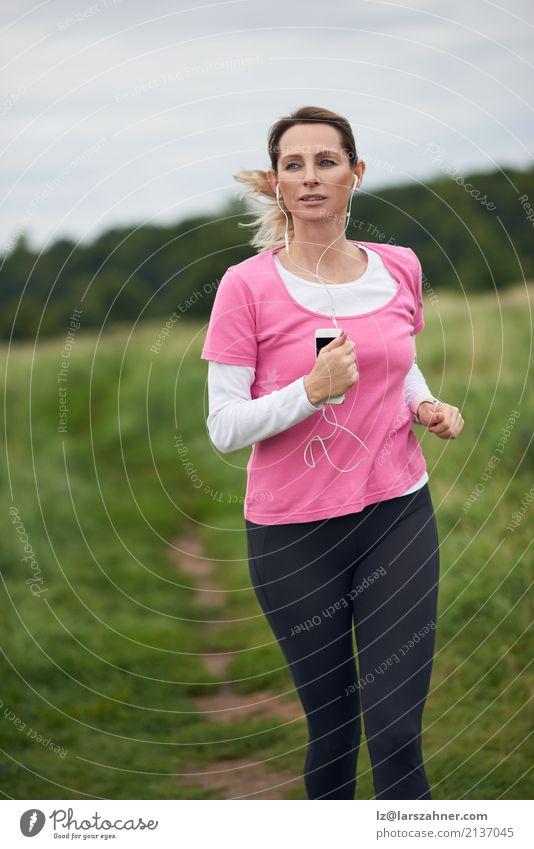 Starke Frau, die durch Feld läuft Mensch Natur Sommer Gesicht Erwachsene Lifestyle Herbst Sport Textfreiraum blond Musik Aktion Fitness hören reif