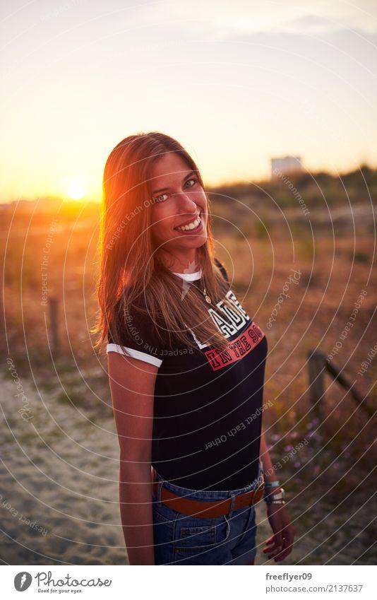 Mädchen, das bei Sonnenuntergang lächelt Lifestyle Ferien & Urlaub & Reisen Tourismus Expedition Sommer Sommerurlaub Strand wandern Mensch feminin Junge Frau