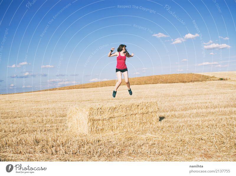 Junge Frau, die auf einem Gebiet des Ernteweizens springt Lifestyle Freude Wellness Leben Ferien & Urlaub & Reisen Abenteuer Freiheit Sommer Sommerurlaub Mensch