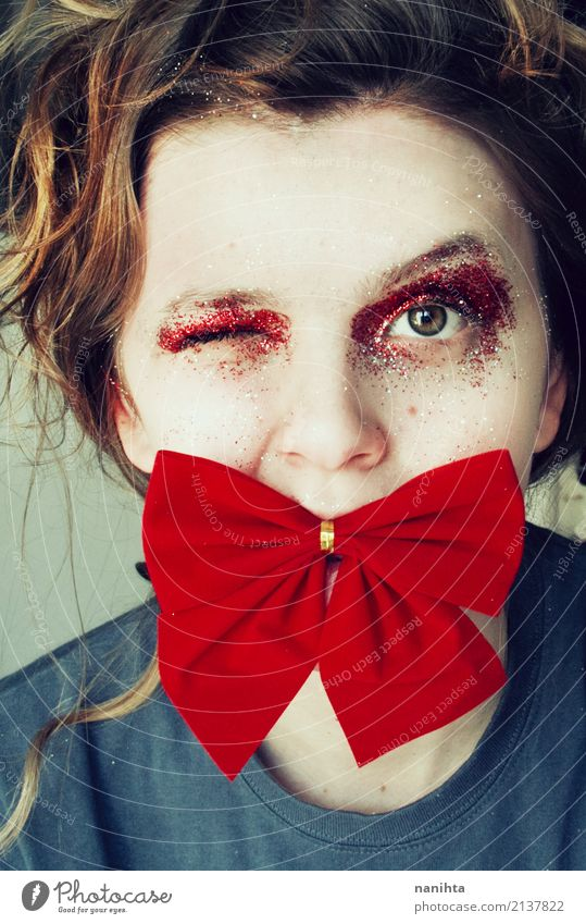 Junge Frau, die ein Auge mit einer Fliege in ihrem Mund blinzelt Lifestyle Stil Schminke Feste & Feiern Weihnachten & Advent Silvester u. Neujahr Mensch feminin