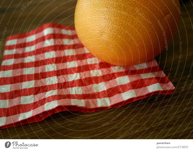 Eine Grapefruit auf einer rot-weiß karierten Serviette auf einem Holztisch. Farben und Firmen. Rund und eckig Lebensmittel Frucht Ernährung Häusliches Leben