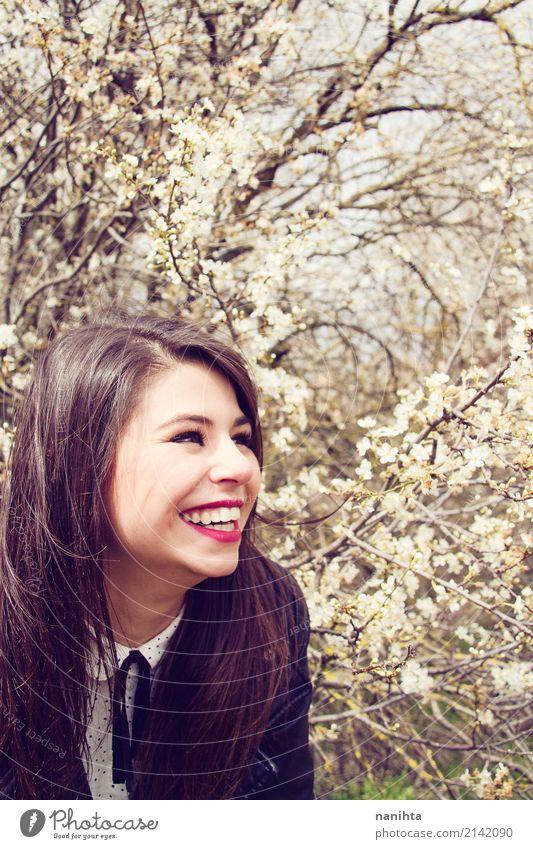 Junge glückliche Frau, die nah an einem blühenden Baum aufwirft Lifestyle Stil Freude Wellness Leben Mensch feminin Junge Frau Jugendliche 1 18-30 Jahre