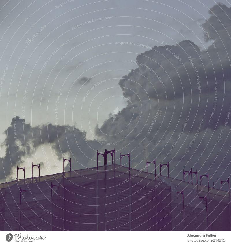 Schlagsahne an Baustelle. Haus Hausbau kalt Baugerüst Abdeckung Wolken dunkel Unwetter Klima Wetter Sanieren Farbfoto Gedeckte Farben Textfreiraum oben Abend