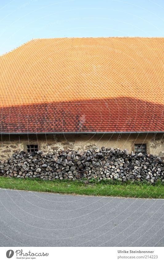 Den Winter im Blick Holz Brennholz Vorrat Haus Scheune Dach Dachziegel Scheite Holzstapel Fenster Mauer grün grünstreifen orange Vorratshaltung vorausblicken