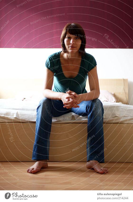 direkt Häusliches Leben Wohnung Innenarchitektur Bett feminin Frau Erwachsene 1 Mensch T-Shirt Hose brünett beobachten sitzen warten authentisch grün rot