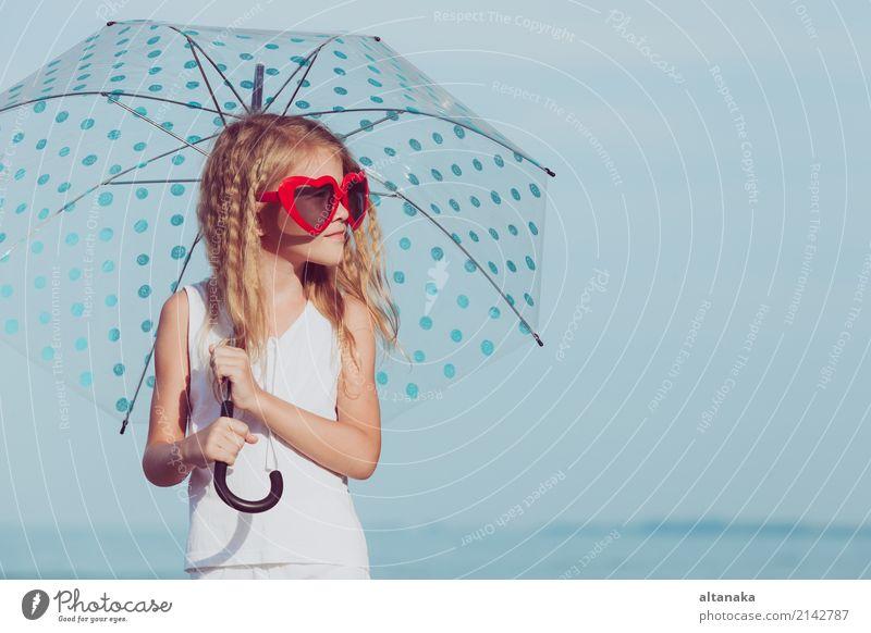 Kleines Mädchen mit dem Regenschirm, der auf dem Strand zur Tageszeit steht Mensch Kind Frau Natur Ferien & Urlaub & Reisen Sommer schön Sonne Meer Erholung