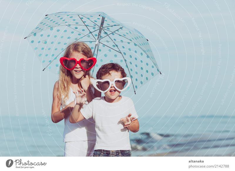 Zwei glückliche Kinder, die am Strand zur Tageszeit stehen Mensch Natur Ferien & Urlaub & Reisen Sommer schön Sonne Meer Erholung Freude Lifestyle Gefühle Sport