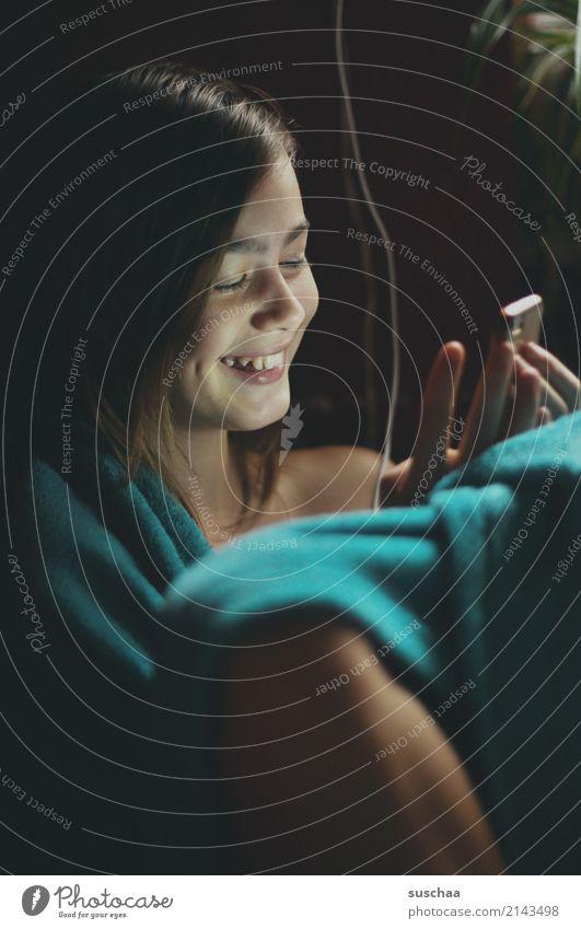 mädchen sitzt lächelnd in eine decke gehüllt und guckt in ihr smartphone Mädchen Kind Jugendliche Junge Frau 13-18 Jahre Internet Telefon SMS Social Media