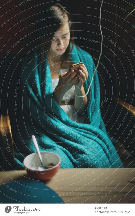 mädchen sitzt in eine decke gehüllt am frühstückstisch und guckt in ihr smartphone Mädchen Kind Jugendliche Junge Frau 13-18 Jahre Internet Telefon SMS