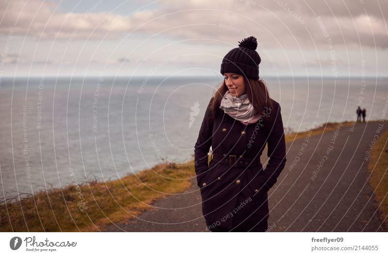 Junge Frau im Winter, der nahe dem Ozean wandert Mensch Himmel Ferien & Urlaub & Reisen Jugendliche Wasser Landschaft Meer Wolken Freude Ferne 18-30 Jahre