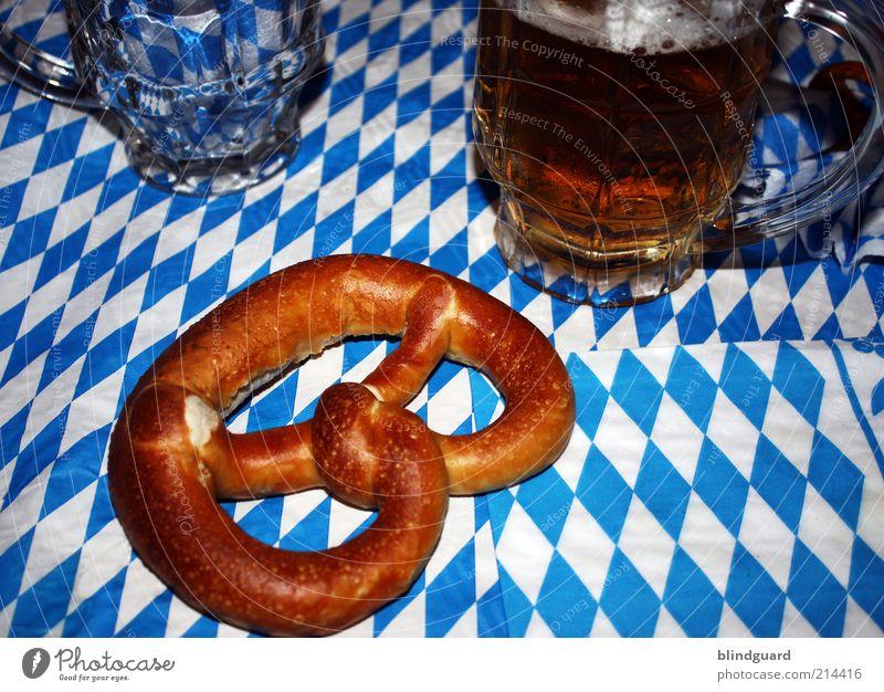 Oktober fest in bayerischer Hand Lebensmittel Getränk Bier Glas Nachtleben Oktoberfest trinken blau weiß Bayern Brezel Muster Schaum Laugengebäck Alkohol