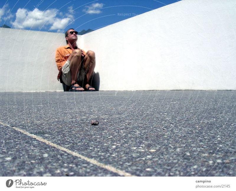 Steinchen Mann Mauer sitzen Perspektive