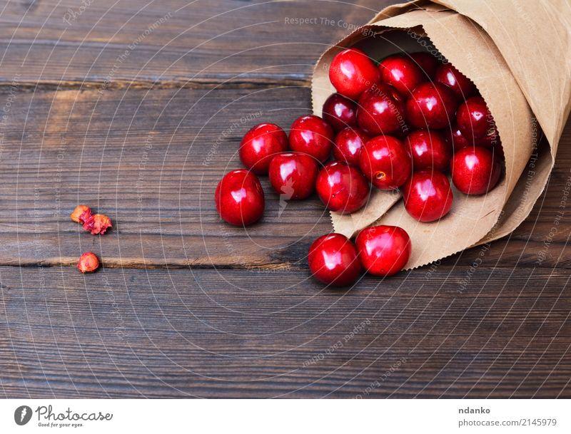 rote Kirsche in einer Papiertüte Frucht Dessert Essen Vegetarische Ernährung Saft Sommer Garten Tisch Natur Holz frisch natürlich oben saftig Hintergrund Beeren