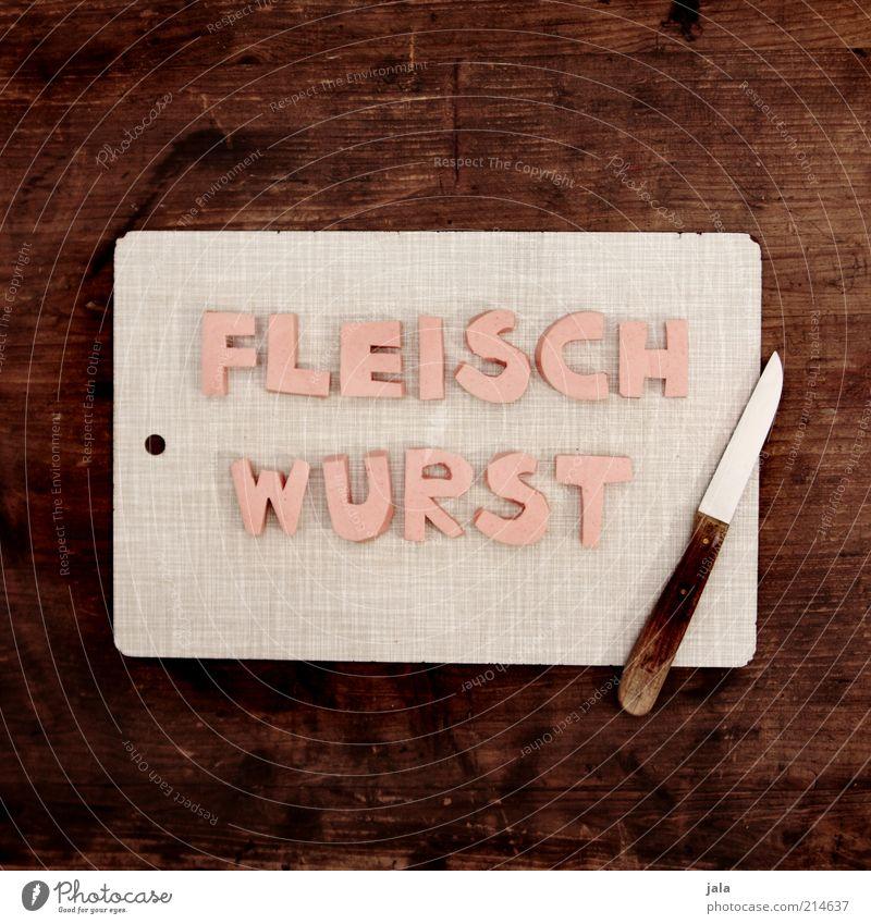 quatschfoto Lebensmittel Fleisch Wurstwaren Ernährung Fingerfood Messer Schneidebrett Holz Schriftzeichen lustig braun grau rosa Fleischwurst Farbfoto
