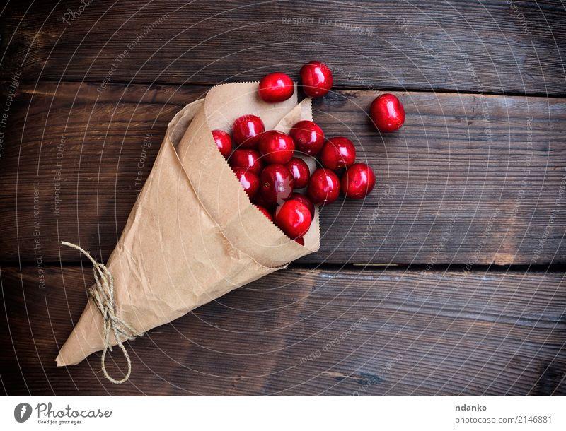 Reife rote Kirsche in einer Papiertüte Frucht Dessert Essen Vegetarische Ernährung Saft Sommer Garten Tisch Natur Holz frisch natürlich oben saftig Hintergrund