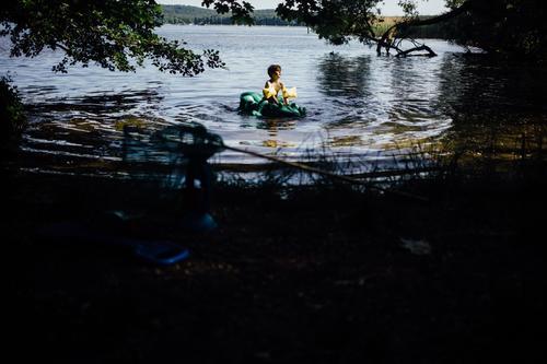 kleiner Junge im Wasser mit Krokodil Luftmatratze Kind Mensch Sommer Sonne Baum Freude Wärme See Schwimmen & Baden maskulin Kindheit genießen heiß Kleinkind