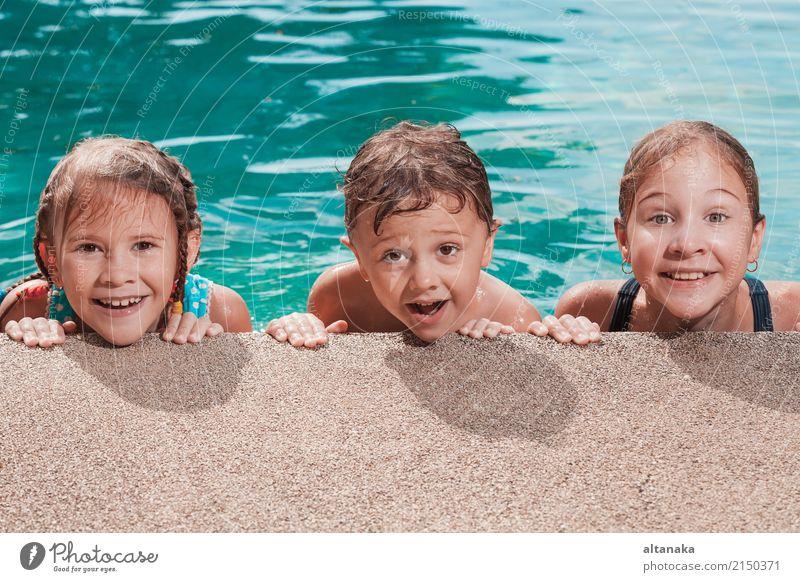 Drei glückliche Kinder spielen auf dem Schwimmbad in der Tageszeit. Menschen, die Spaß im Freien haben. Konzept der freundlichen Geschwister. Lifestyle Freude