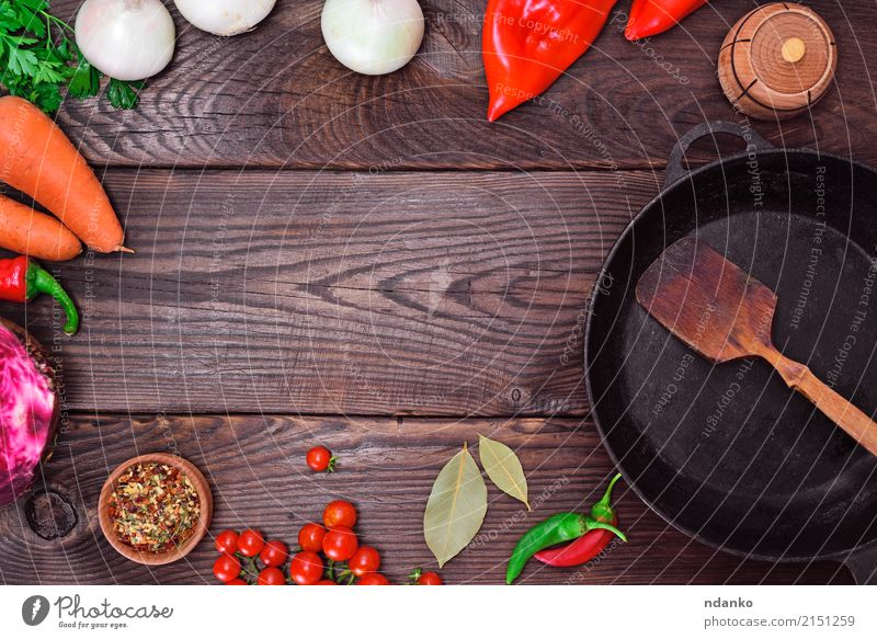 Schwarze Bratpfanne und frisches Gemüse Lebensmittel Kräuter & Gewürze Pfanne Tisch Küche Holz Metall alt rot schwarz Zwiebel Speise Mahlzeit reif Paprika Top