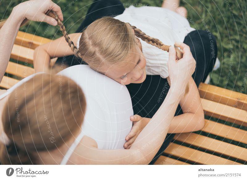 Glückliches kleines Mädchen, das Mutter im Park zur Tageszeit umarmt. Kind Frau Natur Ferien & Urlaub & Reisen Sommer Freude Erwachsene Lifestyle Liebe Sport