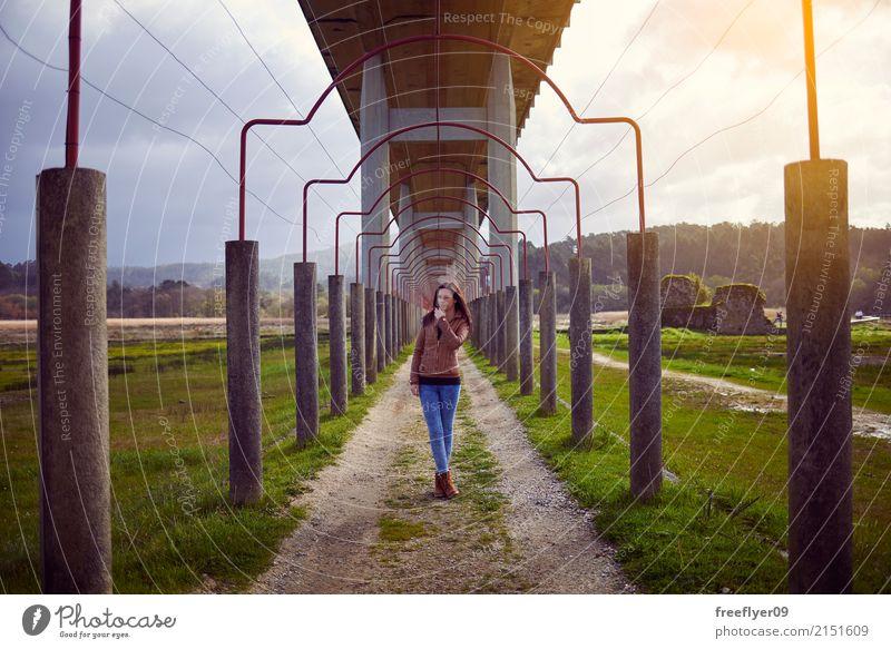 Junges Mädchen, das unter einer Brücke in der Natur aufwirft Mensch Ferien & Urlaub & Reisen Jugendliche Junge Frau Landschaft Freude Ferne Winter 18-30 Jahre