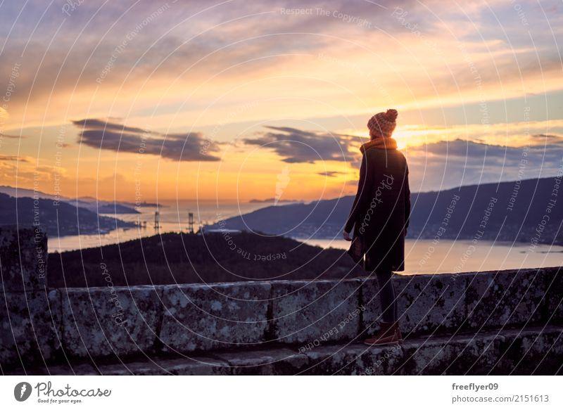 Eine behütete Frau, die den Ozean bei Sonnenuntergang erwägt Mensch Himmel Natur Ferien & Urlaub & Reisen Jugendliche Junge Frau Landschaft Meer Ferne Winter