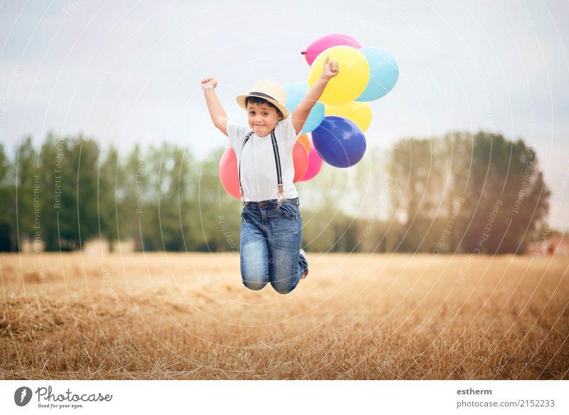 Der Junge springend mit Ballonen auf dem Gebiet Mensch Kind Ferien & Urlaub & Reisen Freude Lifestyle Gefühle Wiese lachen Freiheit Feld Kindheit genießen