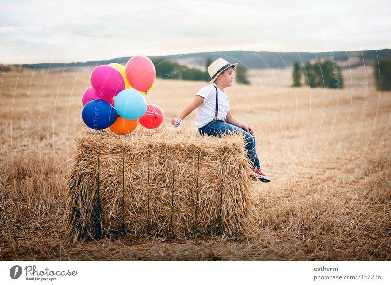 Junge mit Ballonen auf dem Gebiet Mensch Kind Natur Ferien & Urlaub & Reisen Sommer Einsamkeit Freude Lifestyle Frühling Gefühle Wiese Kindheit sitzen