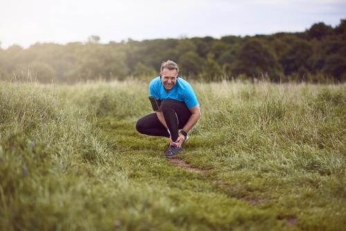 Ein trainierender, laufender Mann klemmt verletzten Knöchel Mensch Landschaft Erwachsene Wege & Pfade Sport Gras Aktion Fitness Medikament anstrengen Wunde