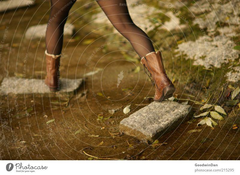 mit großen Schritten Mensch feminin Umwelt Natur Park Bekleidung Strumpfhose Leder Stiefel Stein laufen Stimmung kalt robust Boden Erde dreckig Farbfoto