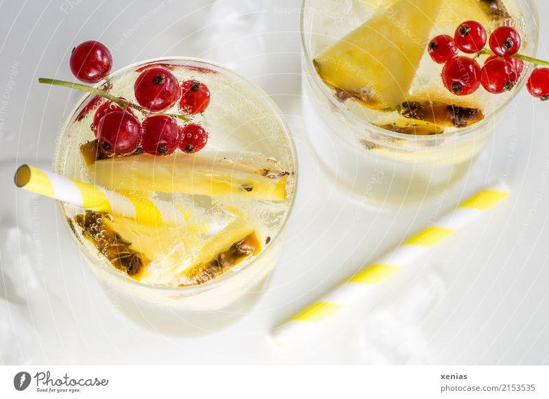 Erfrischendes Getränk mit Ananas, Johannisbeeren, gelben Trinkhalmen und Eiswürfel auf weißem Grund Erfrischungsgetränk Trinkwasser Frucht Limonade Glas